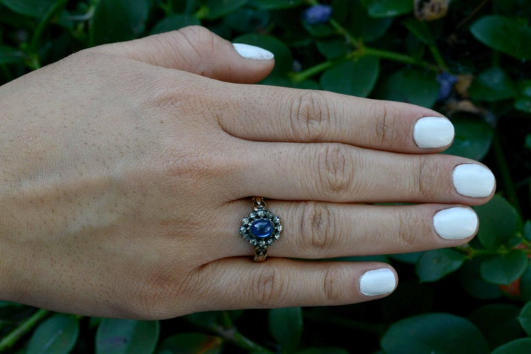 We do not often find treasures from the Georgian era, especially a diamond halo engagement ring from 1830. This original antique features a glowing blue, oval cabochon sapphire and a circle of surrounding rose cut diamonds all set in silver, foil