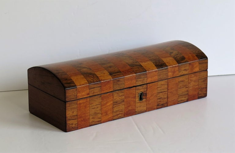 This is a beautiful, fine quality English Georgian period lidded box, inlaid with crossbanded mahogany and satinwood with a hinged domed lid, dating to circa 1810.