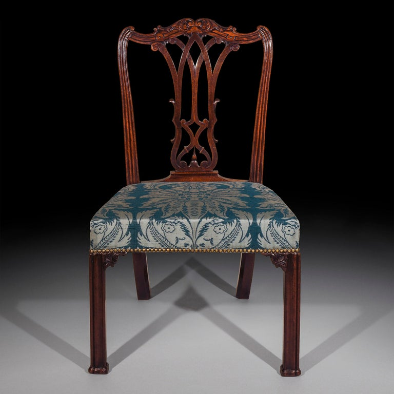 Fine George III period mahogany side chair of outstanding quality, in the style of Thomas Chippendale's 'Director'.   English, circa 1765.   With a shaped foliate carved crest rail over a pierced gothic splat back and a traditionally upholstered