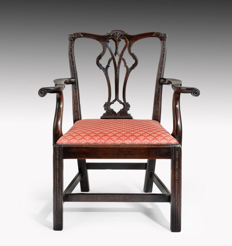 A George III Chippendale period mahogany armchair; the scrolling top rail carved with a central acanthus leaf above a pierced splat and bold outscrolling arms. The armchair has an upholstered drop-in seat and is raised on square moulded legs which