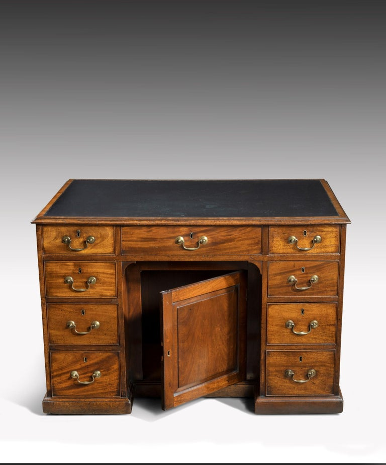 A Georgian Chippendale period mahogany pedestal desk, the desk's leathered top crossbanded in mahogany above three frieze drawers to the front with a central recessed panelled door flanked by banks of three graduated drawers, to the rear of the desk