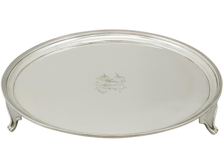 A fine and collectable antique Georgian English sterling silver salver made in York; an addition to our silver ornamental collection.  This fine antique George III sterling silver salver has a plain circular rounded form onto three bracket style