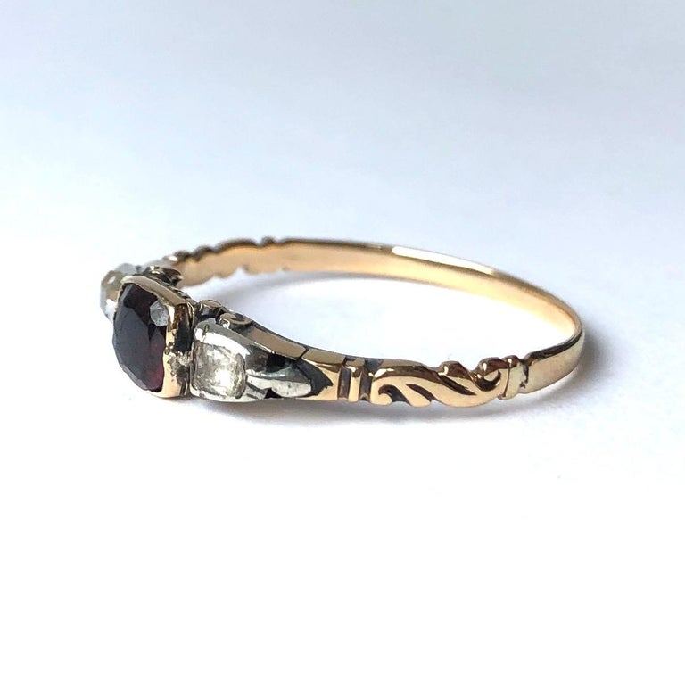 At the centre of this three stone ring there is a deep glossy red garnet and either side of this stone sits 1 rose cut diamond and one paste. The settings and shoulders are typically Georgian and the shoulders have some really lovely detail to them.