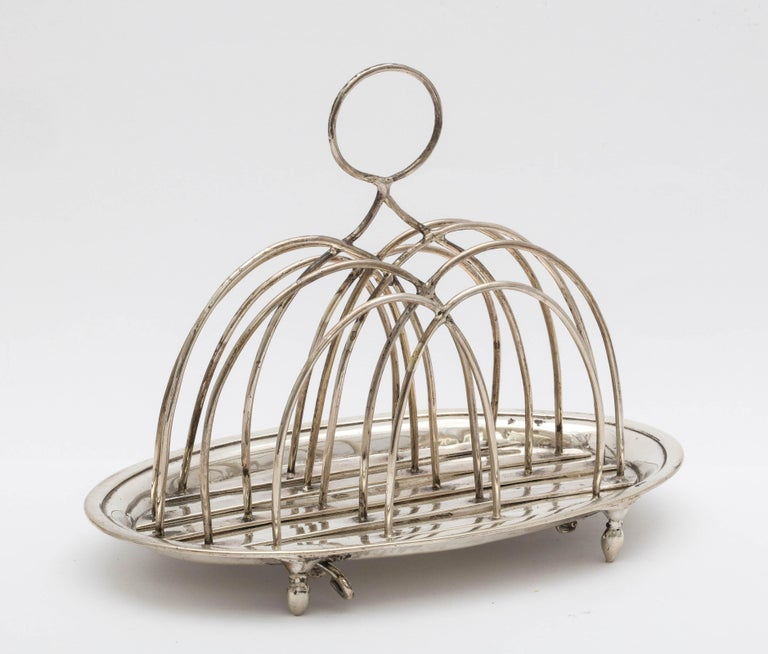 Georgian (George III), sterling silver, footed toast rack, London, 1784, Barrage Davenport - maker. Measures 5 inches to top of handle x 6 inches wide x 3 3/4 inches deep. Silver wire separators are removable for cleaning (see photos of underside of