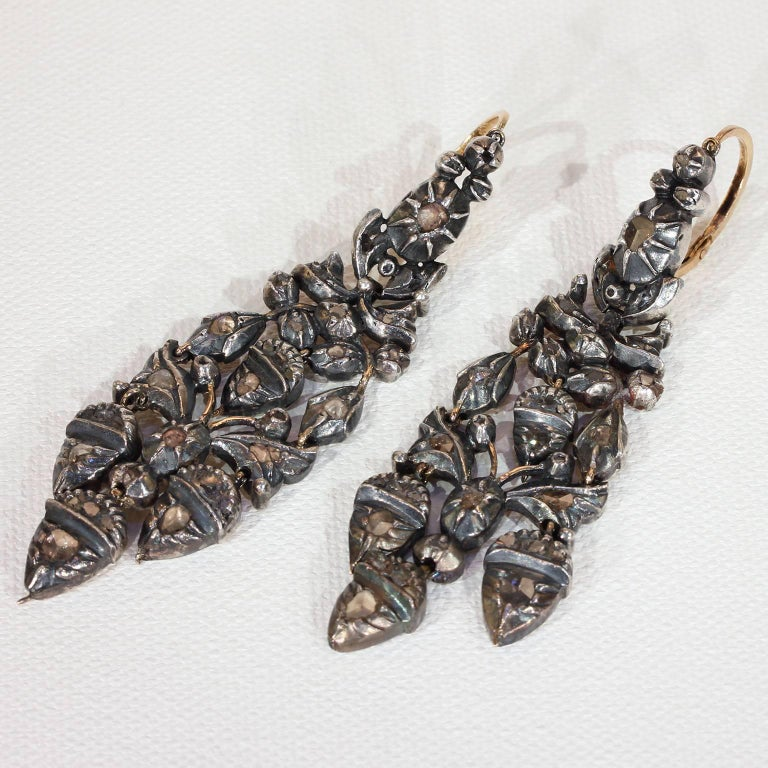 These fabulous, long statement earrings were hand crafted in the Georgian era, around 1780. They feature an acorn and oak leaf motif and are set with table cut rose diamonds. These earrings are sterling silver over 14 karat gold and are probably