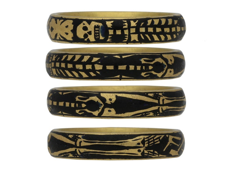 Georgian gold and enamel memorial skeleton ring. A solid D-shape gold band featuring an elongated skeleton with stylised skull and cross bones motif on a black enamel background, engraved on the inside in italic script and infilled in black enamel