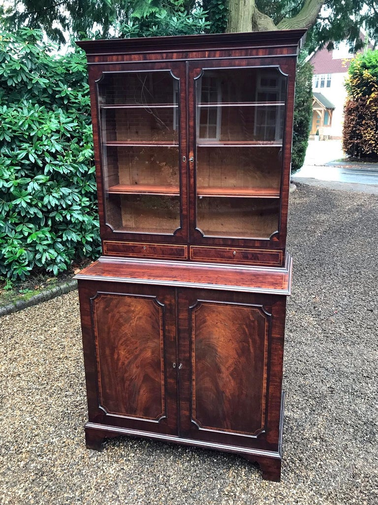 A high quality Georgian mahogany bookcase and cupboard with adjustable shelves to the glazed section and two drawers below. Complete with the original 8 sliding trays in the cupboard below on bracket feet. Comes apart in two separate sections, circa