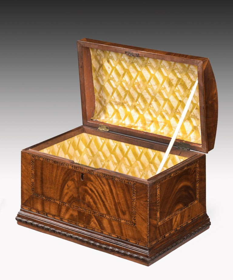 A superb Georgian mahogany domed box; the domed lid veneered in well figured mahogany and inlaid with feather banding and barber's pole stringing and retaining its original fire gilded handle; the sides veneered in flame mahogany and crossbanded in