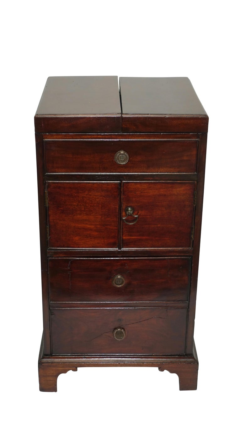 Georgian mahogany washstand with flip open top, the inside fitted with lift up above a false drawer, a pair of doors open to reveal cabinet space above a deep drawer, standing on bracket feet with brass handles on either side. Showing signs of early