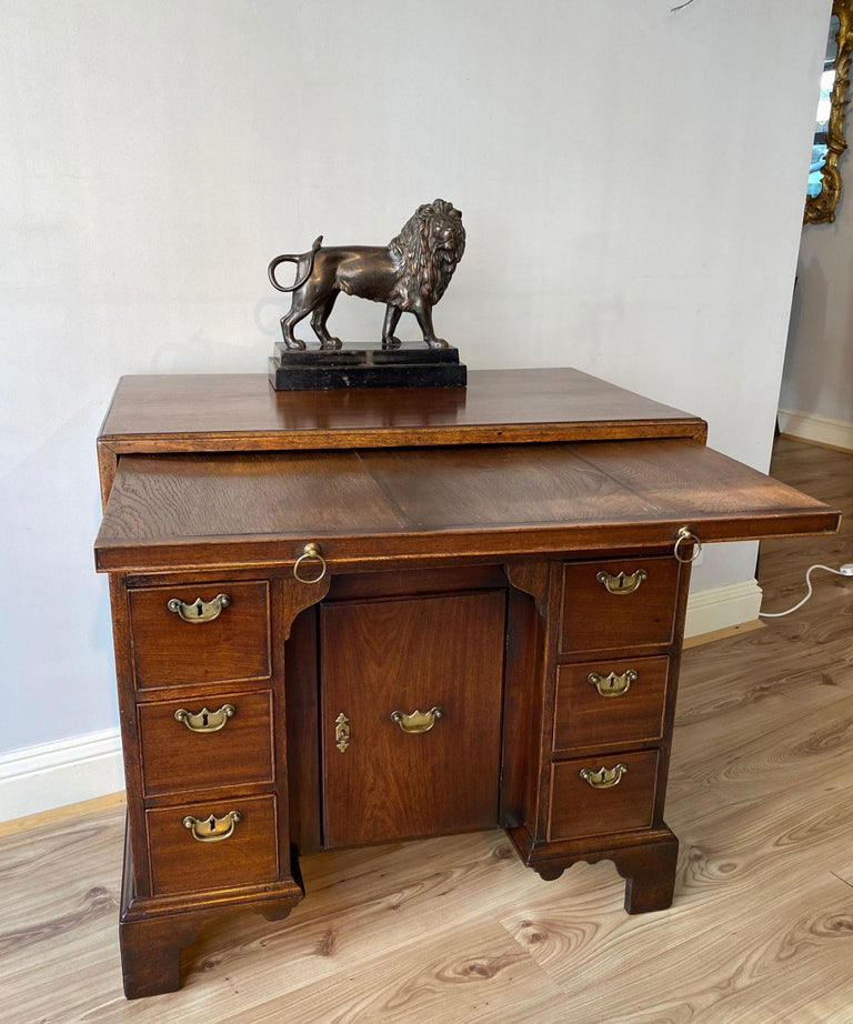 A fine George II mahogany kneehole desk with cabinet-maker or retailer's label for Lowdell, Southwark. The desk's caddy moulded top above a brushing slide and a long drawer; having a central pull-forward door flanked by banks of three graduated