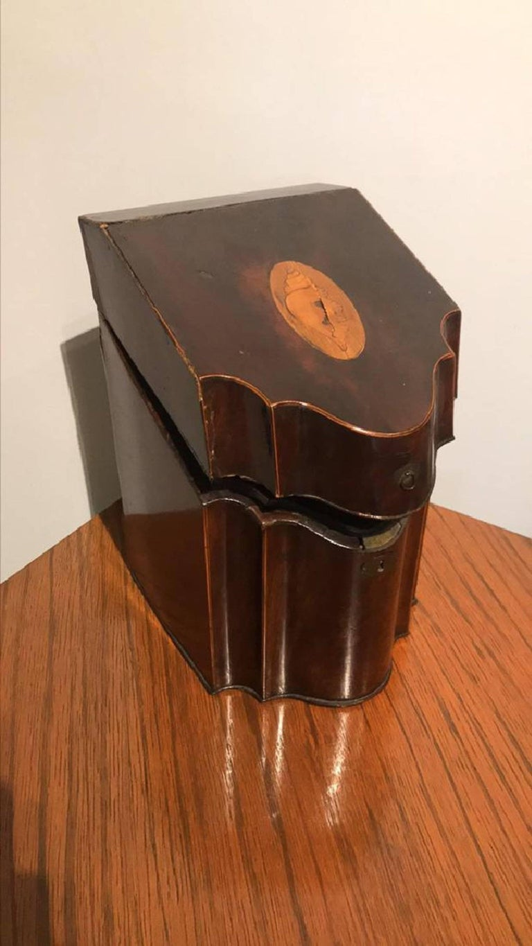 19th century Georgian mahogany slope top and shaped front liqueur box. The satinwood conch shell inlaid top opens to a fitted interior having hand blown gold overlay bottles.  One bottle has chipped lip, box is in old antique condition, good for