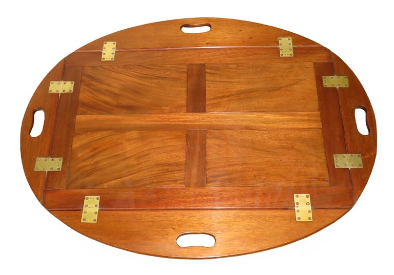 A good quality Georgian mahogany oval butlers tray Of panelled form having original brass hinges to Folding sides raised on later square Tapered leg stand  (Always a great solution to the age old  problem of there being no such thing a