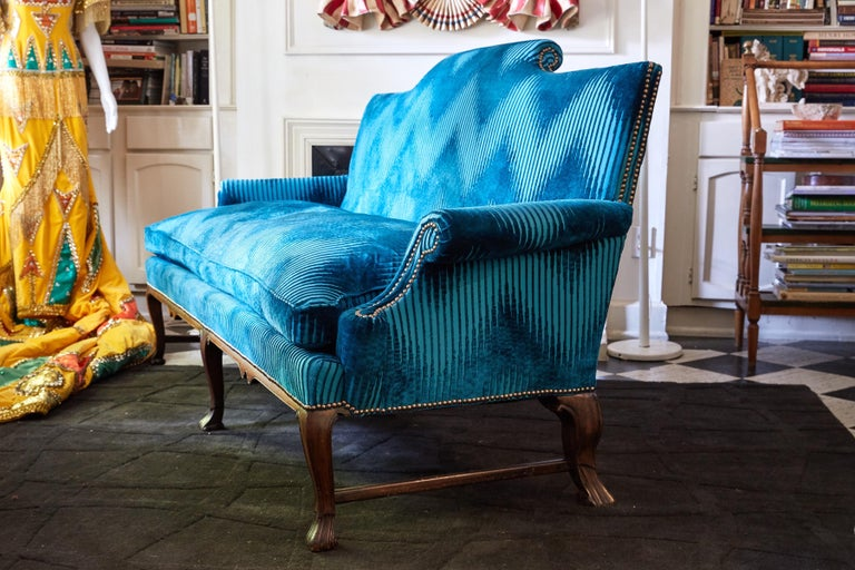 19th century English sofa in the Georgian style with a carved mahogany frame. The sofa has a cushion back and one cushion down seat. It has been reupholstered in turquoise Jim Thompson Bargello fabric and accented with rose gold nailheads.