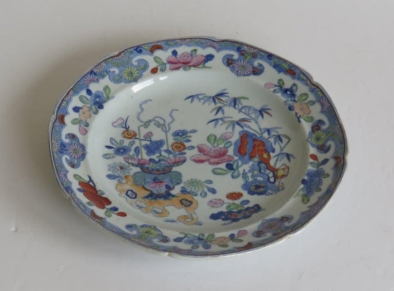 This is a very decorative dish or plate by Mason's Ironstone, Lane Delph, England in the Bamboo and Basket pattern, dating to the early 19th century, Georgian period, circa 1813-1820.  The plate or dish is fairly deep and circular in shape with a