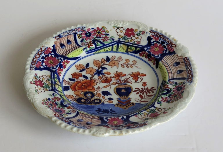 This is an early and very decorative ironstone pottery side plate or dish produced by the Mason's factory at Lane Delph, Staffordshire, England, circa 1815.  The plate is circular with an attractive pie crust edge moulding to the rim.  This