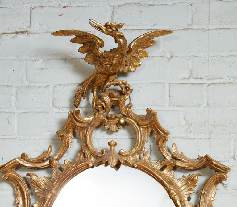 Fire George III period oval giltwood mirror, having phoenix carved crest over rococo scroll and foliate carving, the mercury glass oval plate crowned with naturalistic pagoda hood and flanked by elongated