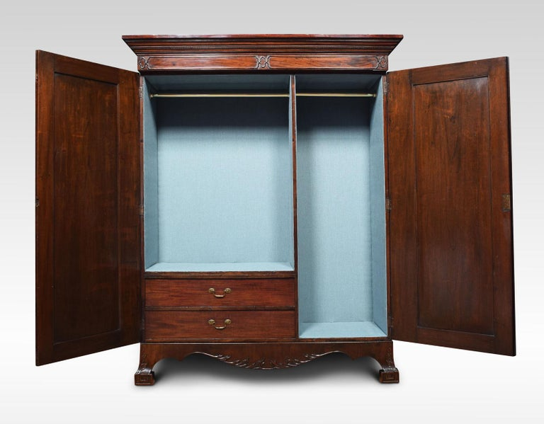 George III style mahogany wardrobe. The outset cornice above a moulded frieze and two paneled blind fret doors opening to reveal hanging space and two short drawers to the base with brass swan-neck handles. All raised up on large bracket