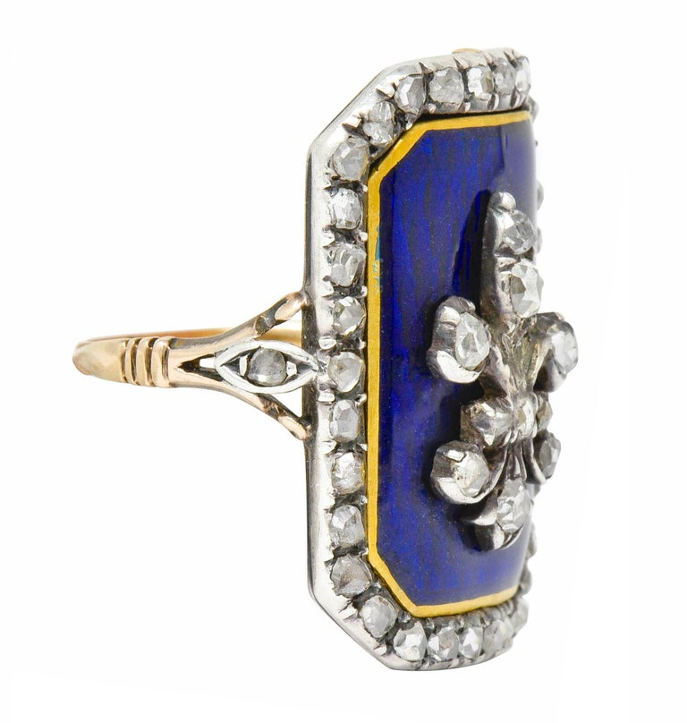 Statement ring designed as a rectangular mounting with a slight bow for a comfortable fit,  Centering a fleur-de-lis emblem with a bright royal blue enamel background with a gold enamel border; exhibiting no loss  Set throughout by rose cut diamonds