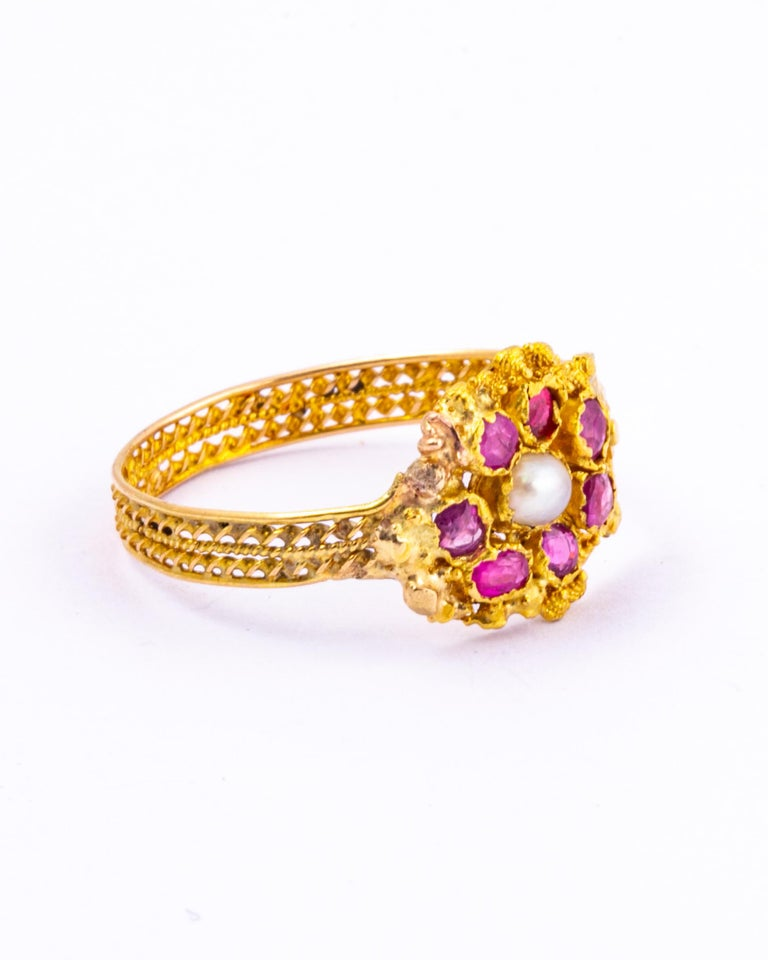 This stunning ring has so much detail. There are seven rose cut rubies and a pearl sat at the centre. Surrounding the stones is intricate cannetille work and the band is made up of fine twisted gold.   Ring Size: R or 8 1/2  Width: 11mm  Weight: 1.7g