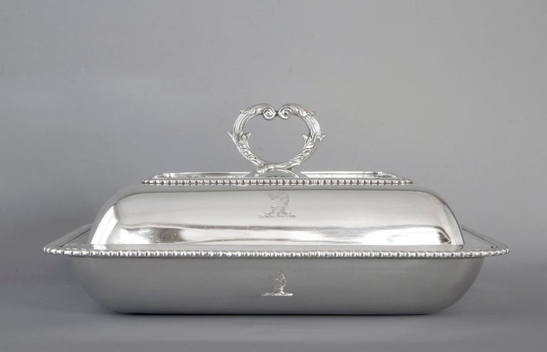An excellent quality George III solid silver entree dish of shaped rectangular cushion form. Decorated with gadrooned borders to base and cover, both have an engraved crest see pictures. The removable cast silver handle with matching decoration.