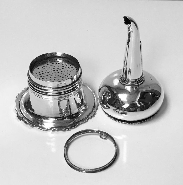 Antique Georgian silver wine funnel, London 1828, John Terry. The Funnel with campana base with foliage surround, bulbous body, strap work funnel, plain shield like thumbpiece. Muslin ring to interior. Marked on body and base. Measures: Height 6.25