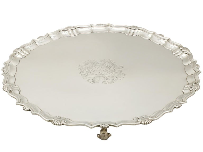 A fine and impressive, large antique Georgian English sterling silver salver made by John Tuite; an addition to our dining silverware collection.  This fine antique George II sterling silver salver has a plain circular shaped form.  The surface