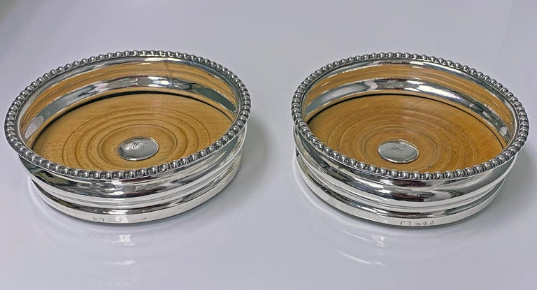 Antique Georgian sterling silver wine coasters, city of Sheffield 1810, Thomas Blagden. Each of circular rounded shaped form, plain ribbed bodies, gadroon borders. Original turned wood bases, central silver bosses with letter R. Baize to undersides.
