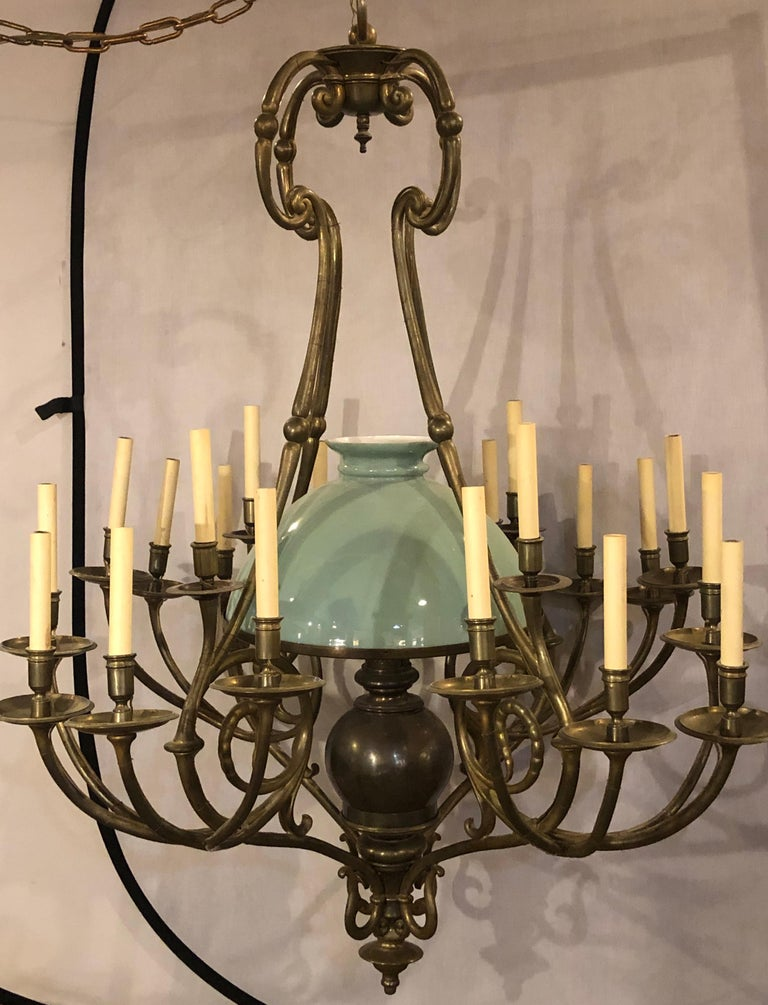 An early 1900s Georgian style chandelier with a globe centre matching chain and canopy. A wonderful bronze form twenty one light chandelier having four arms sets of five lights each with a centre green globe taking one large bulb. The whole recently