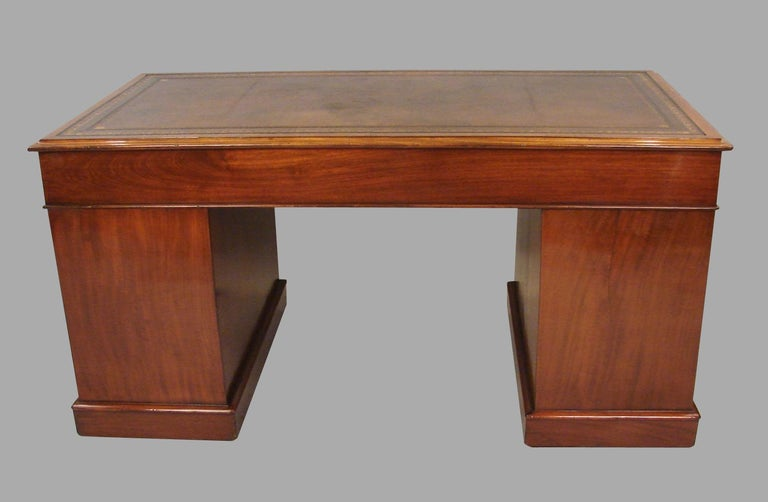 A good Georgian style mahogany pedestal desk, the brown gilt-tooled leather top above 3 frieze drawers over 2 pedestals with 3 further drawers all resting on a plinth base with concealed casters. Locks signed Parkes Miller Hall, London, circa 1870.
