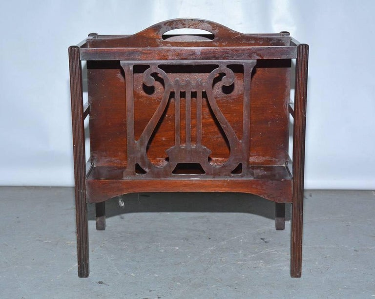 The Georgian style two-section magazine rack or canterbury is made of mahogany veneer. The sides have a lyre design, there is a handle, and possibly the unit was used for sheet music.