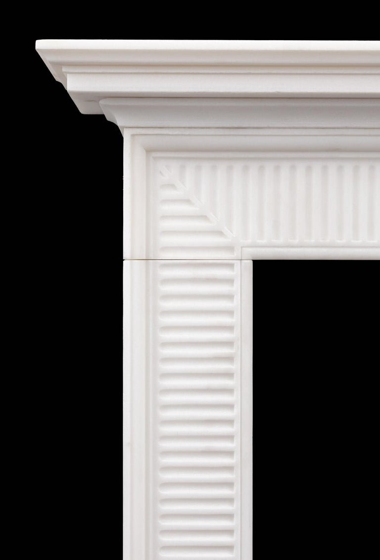 A pure white marble fireplace of refined late Georgian design. The wide molded frame is carved with finger flutes that come to a mitre in each corner, this with cornice shelf resting on top.  The Wilton mantelpiece is based on an 18th century