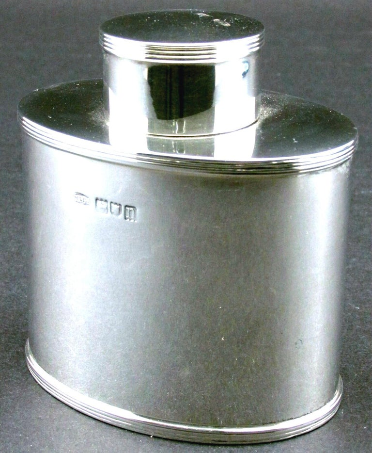 Of timeless design, this very fine & heavy sterling silver tea caddy is clearly inspired by the Georgian period showing an oval shaped canister decorated with an elegant reeded border to both the shoulder & base, the neck fitted with a snug fitting