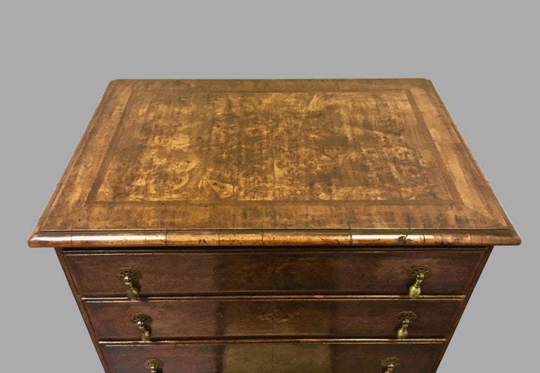 An inlaid burl walnut veneered Georgian style four-drawer chest of desirable small size, the crossbanded top with a molded edge above 4 graduated short drawers with brass teardrop pulls, the sides with crossbanded edges, all supported on square
