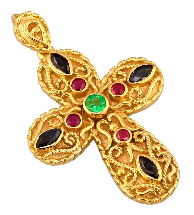 This S.Georgios Designer Byzantine Style Cross Pendant Enhancer is handmade from solid 18 Karat Yellow Gold and features 4 Rubies, 4 Sapphires, and an Emerald center with all total weight of 1.05 Carat. This stunning art piece is made as an