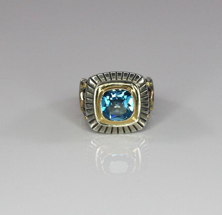 S.Georgios designer unisex Two-Tone ring all handcrafted from sterling silver and solid 18 Karat yellow gold pieces - crowns picturing different symbols that create a unique medieval look. The ring features a Cushion cut Sky Blue Topaz with a total