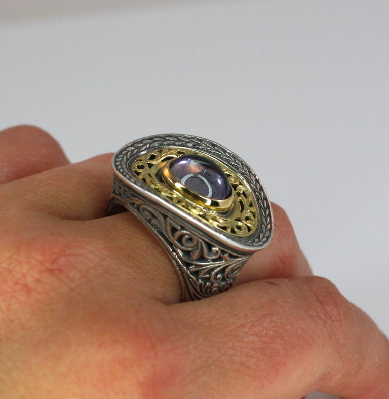 Presenting an asymmetrical oval all handmade heavy decorated ring crafted from sterling silver and solid 18 Karat yellow gold to create a unique look. The ring features 2-carat cabochon amethyst. Please contact us for this design in a different