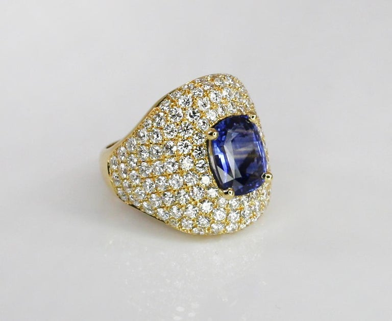 This S.Georgios gorgeous designer wide band Sapphire and Diamond Ring in 18 Karat Yellow Gold and all hand made. It features a stunning oval shape natural Sapphire total weight of 4.53 Carat encircled by natural white Diamonds brilliant cut VVS2