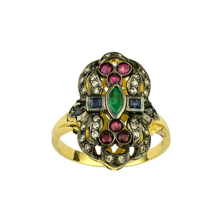 S.Georgios designer 18 Karat yellow gold ring handmade and decorated with Byzantine-style granulation and a combination of Diamonds, Rubies, Sapphires, and a center Emerald. The ring features brilliant cut diamonds total weight of 0,22 Carat, and