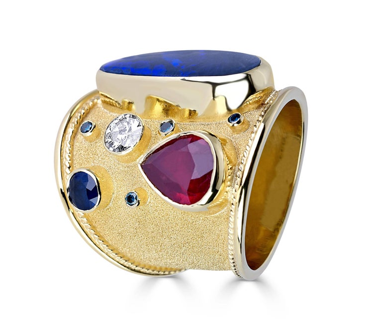 Unique S.Georgios designer 18 Karat Solid Yellow Gold Ring all handmade with the Byzantine workmanship and a unique velvet background. This one of a kind ring features a 5.40 Carat Opal, 2.44 Carat Ruby, 0.50 Carat Sapphire, 0.38 Carat White