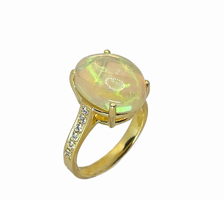 This S.Georgios designer 18 Karat Yellow Gold Natural Australian Opal ring is all custom made by hand and features a stunning cabochon cut Natural beautiful color Opal total weight of 4.48 Carat. We have accented this gorgeous Opal art piece with 12