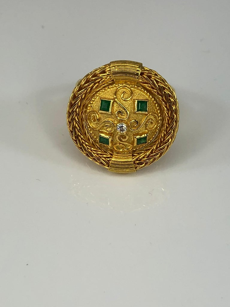 Presenting S.Georgios designer 18 Karat yellow gold ring handmade and decorated with Byzantine-style granulation and handknitted rope all around the edge. The center decorates 0.02 Carat brilliant cut diamond and 4 princess cut emeralds total weight