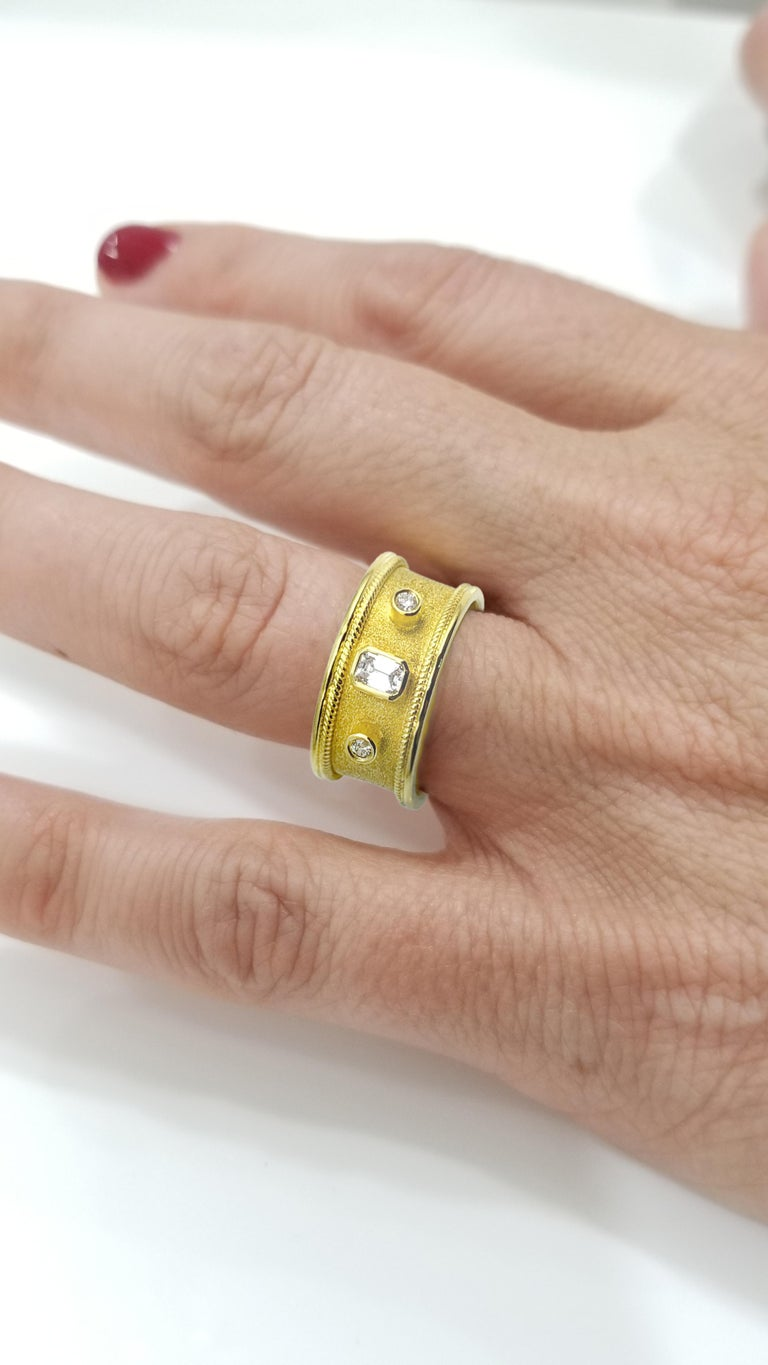 S.Georgios designer ring in solid 18 Karat Yellow Gold all handmade with granulation workmanship in Byzantine style and a unique velvet look on the background. This beautiful band ring features an Emerald cut White Diamond total weight of 0.20 Carat