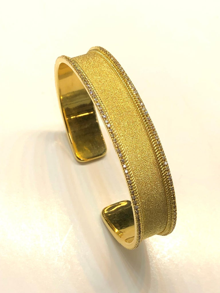 S.Georgios designer bangle bracelet hand made in 18 Karat yellow gold. This bracelet is finished in Byzantine style with the unique velvet look on the background. The bracelet features brilliant cut white diamonds total weight of 0.86 Carat around