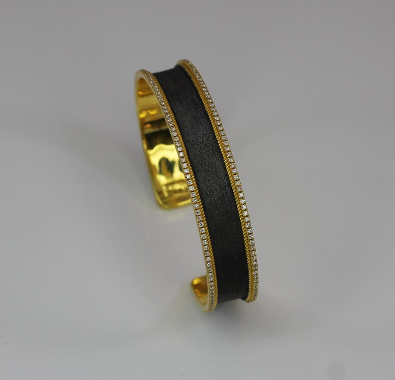 S.Georgios designer 18 Karat yellow gold two-tone bangle stackable Bracelet all custom made by hand and features 2 rows of Brilliant Cut White Diamonds total weight of 1.15 Carat. This stunning piece has granulation work and is microscopically