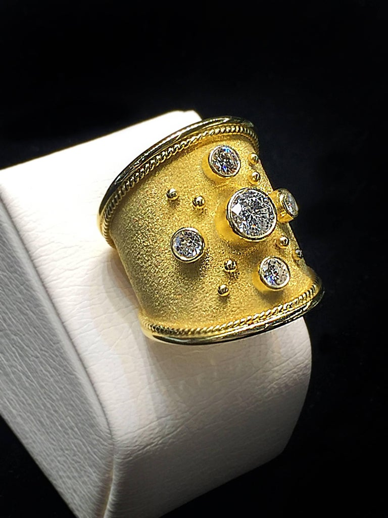 S.Georgios designer 18 Karat Yellow Gold Wide Band Ring is all hand made and has Byzantine granulation beads and wires from 22 Karat gold and a unique velvet look on the background done all microscopic. The gorgeous ring features a center Brilliant