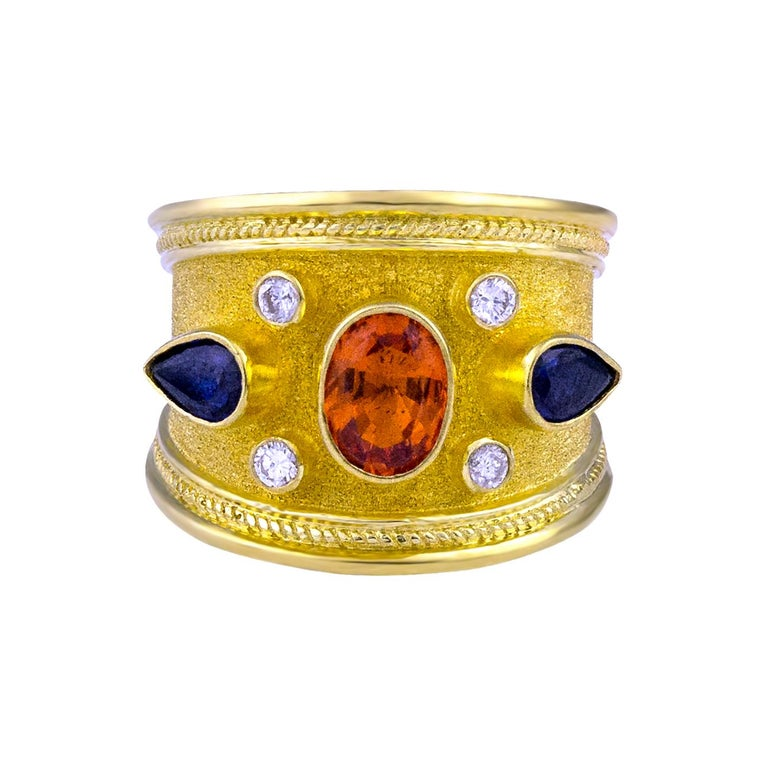S.Georgios Hand Made 18 Karat Yellow Gold Ring decorated with Byzantine-style granulation and the unique velvet finish on the background. The ring features 4 Diamonds total weight of 0.20 Carat and 3 Sapphires. In the center we have an Oval Orange