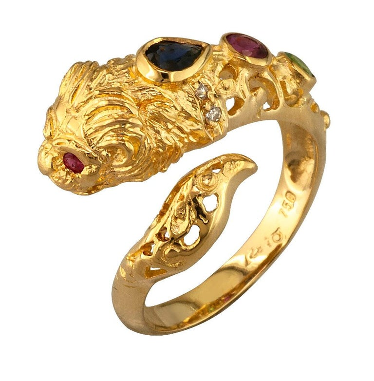 This S.Georgios unique designer Lion Band Ring is 18 Karat Yellow Gold and all handmade with granulation workmanship creating a stunning Lions head, A Greek symbol of strength. This gorgeous band ring features a pear-cut Blue Sapphire, 3