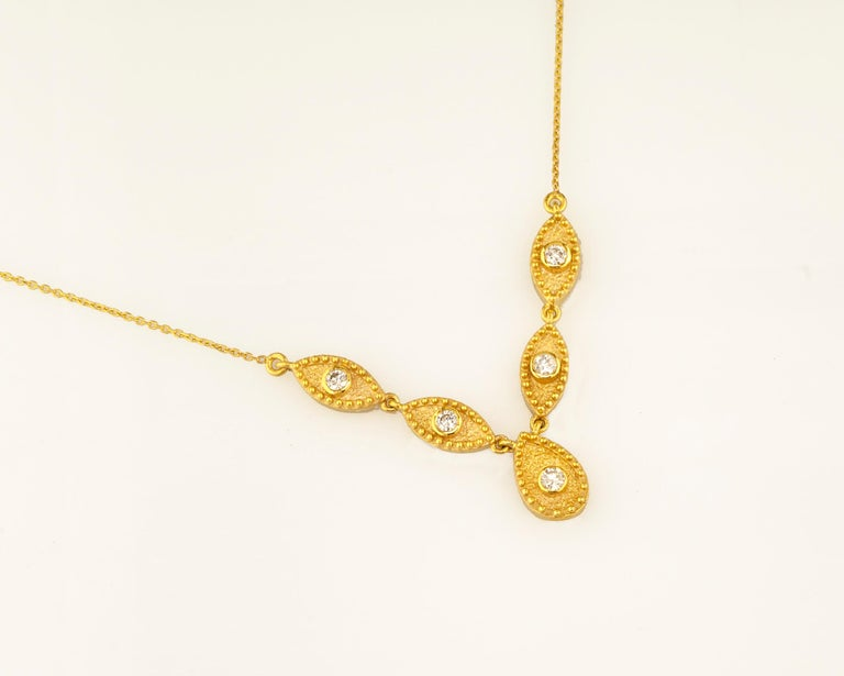 This S.Georgios designer 18 Karat Yellow Gold drop diamond pendant necklace is microscopically decorated with Byzantine granulation work and finished with a unique velvet background look. This beautiful Necklace showcases 5 brilliant-cut Diamonds