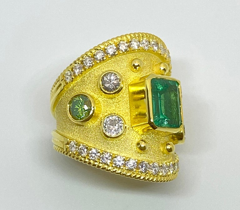 This S.Georgios designer 18 Karat Yellow Gold Band Ring is all handmade with a Byzantine Granulation Workmanship and a unique velvet background. This gorgeous band features in the center an Emerald cut natural Emerald total weight of 1.65 Carats, 4