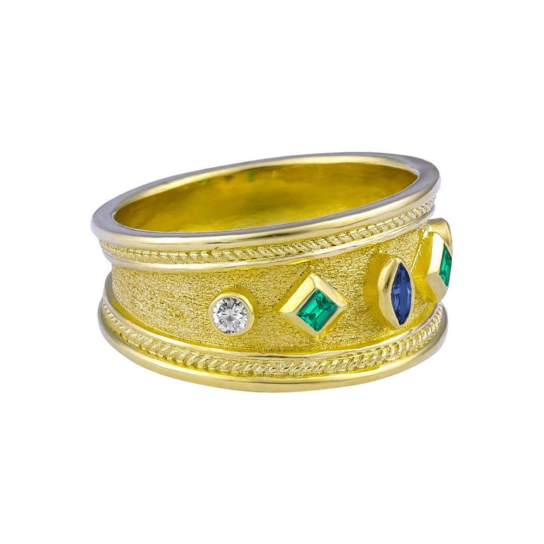 S.Georgios designer 18 Karat Solid Yellow Gold Band Ring is all handmade with Byzantine granulation workmanship and a unique velvet background. The gorgeous ring features a center 0.10 Carat Marquise Sapphire and on the sides, 2 natural Emeralds